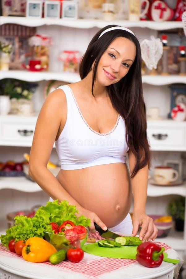 A mulher gravida de sorriso nova corta vegetais na salada fotos de stock royalty free