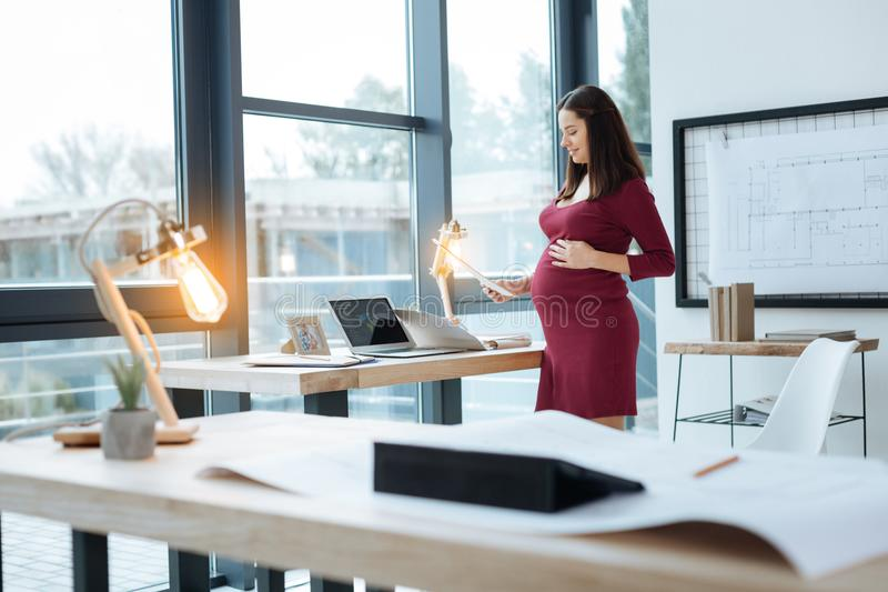 Mulher gravida de sorriso ocupada com trabalho imagem de stock royalty free