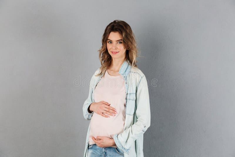 Mulher gravida de sorriso que guarda sua barriga e vista da câmera fotografia de stock royalty free