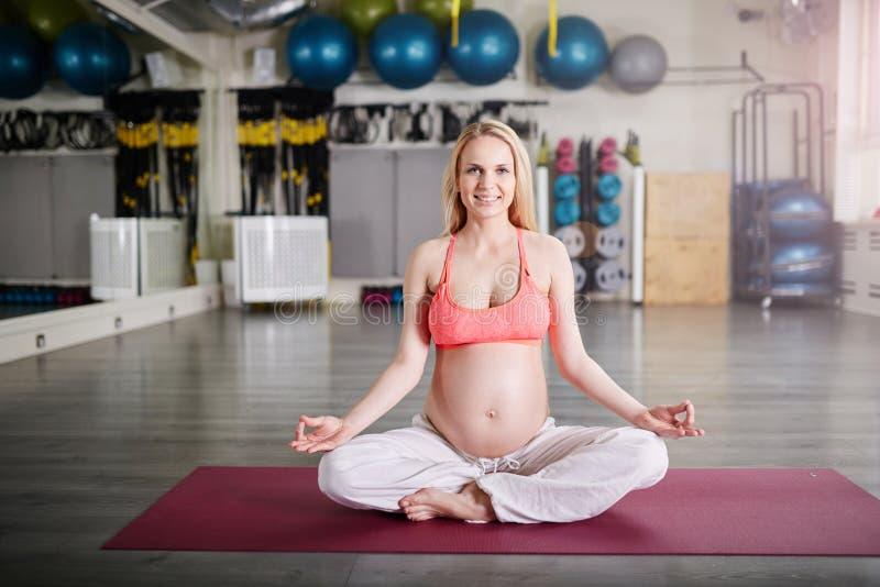 Mulher gravida de sorriso que medita na pose da ioga fotos de stock royalty free