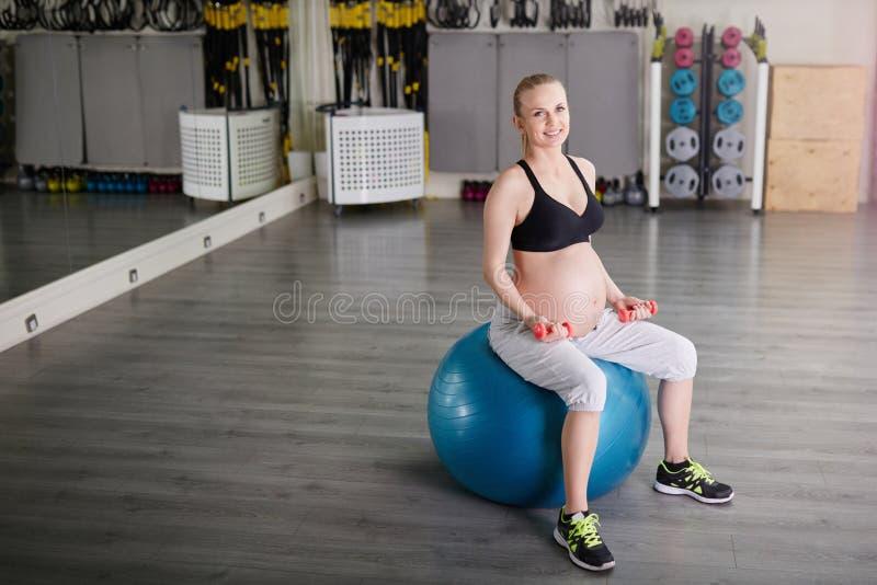 Mulher gravida de sorriso que senta-se em levantar peso da bola do gym fotografia de stock