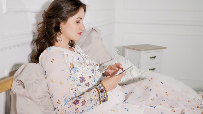 Mulher gravida de sorriso que que senta-se na cama e em usar o smartphone na casa foto de stock royalty free