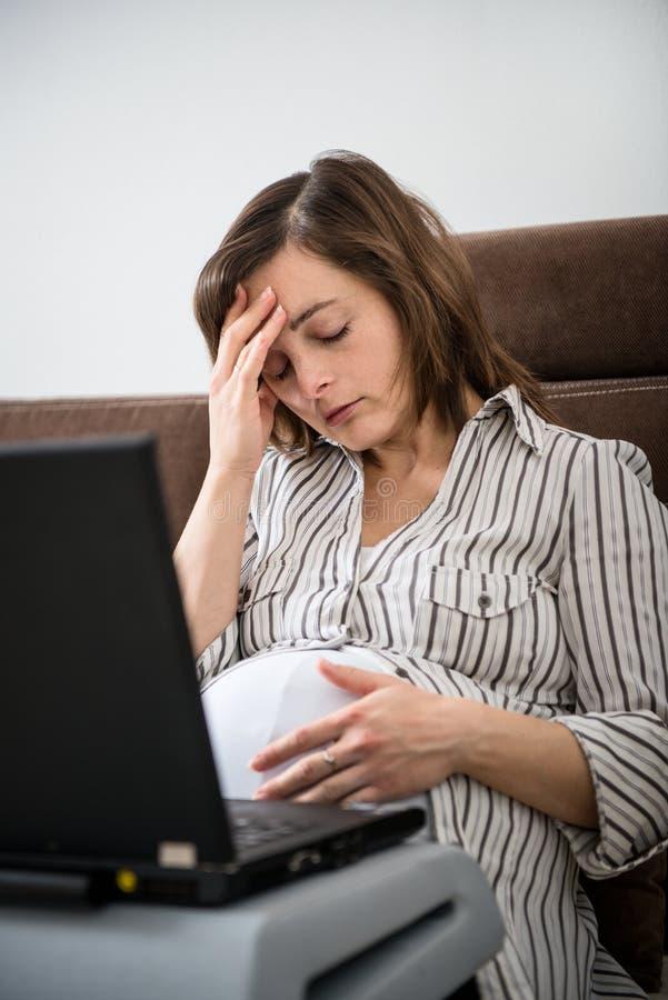 Mulher gravida de trabalho com dor de cabeça imagens de stock royalty free