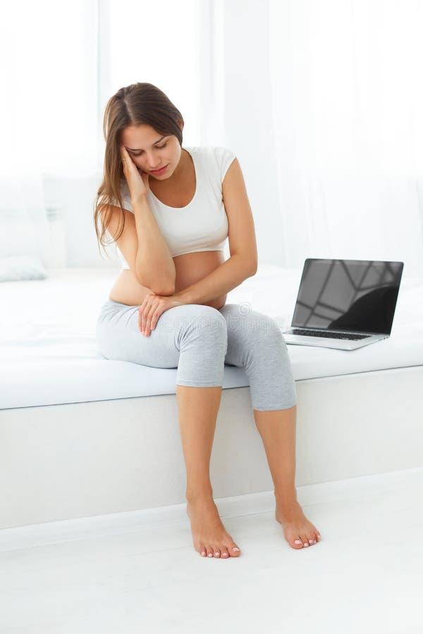 Mulher gravida deprimida com um laptop ao sentar-se sobre foto de stock