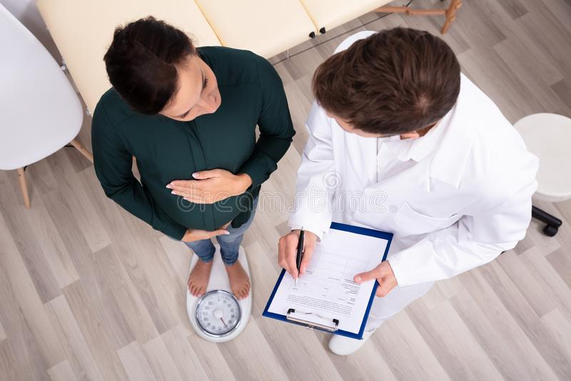 Mulher gravida do doutor Measuring Weight Of foto de stock
