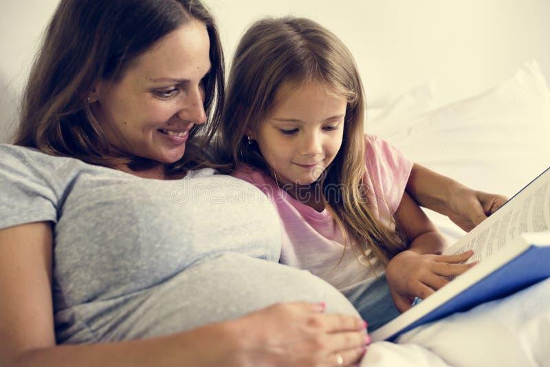 Mulher gravida e livro de leitura do daugther junto na cama imagens de stock