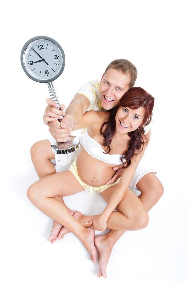 Mulher gravida e marido com o pulso de disparo que mostra nove foto de stock