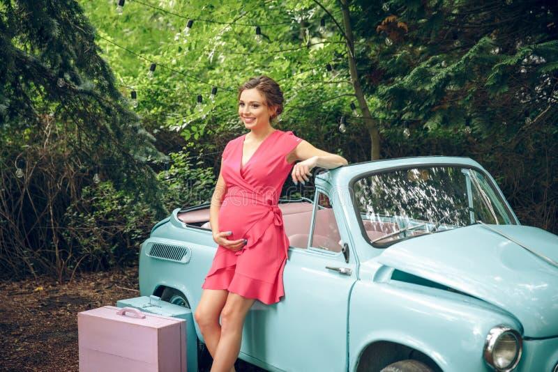 A mulher gravida e o carro retro estacionaram na rua velha da cidade fotografia de stock royalty free