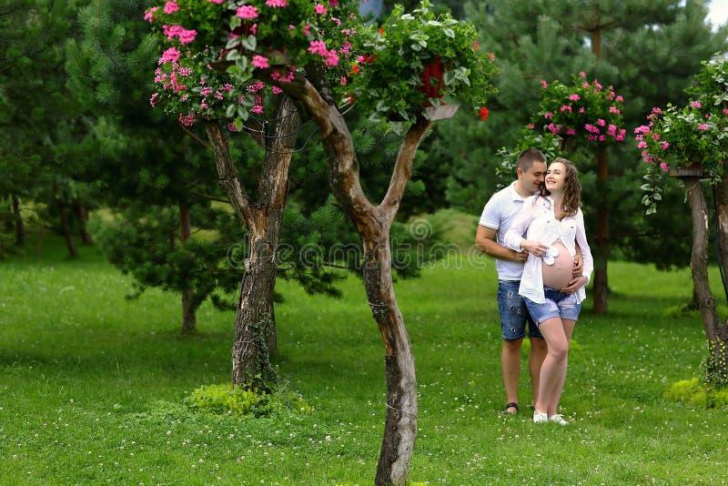 Mulher gravida e seu homem de amor que levantam no parque Imagem autêntica do estilo de vida Lugar para o texto fotografia de stock
