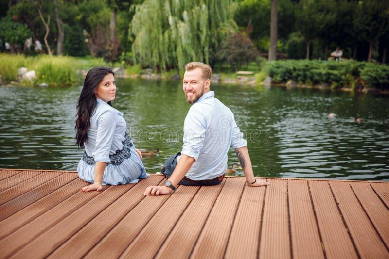 Mulher gravida e seu marido em um parque perto do aperto da água fotos de stock royalty free