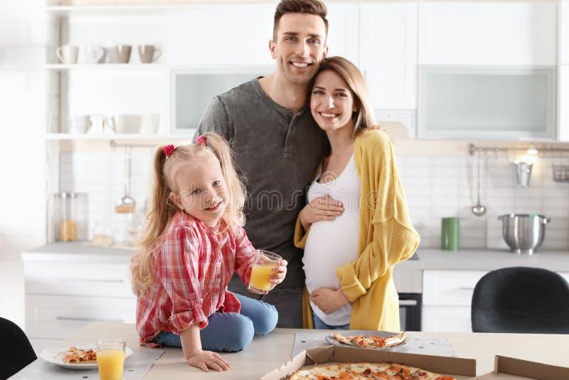 Mulher gravida e sua família que comem a pizza fotos de stock royalty free