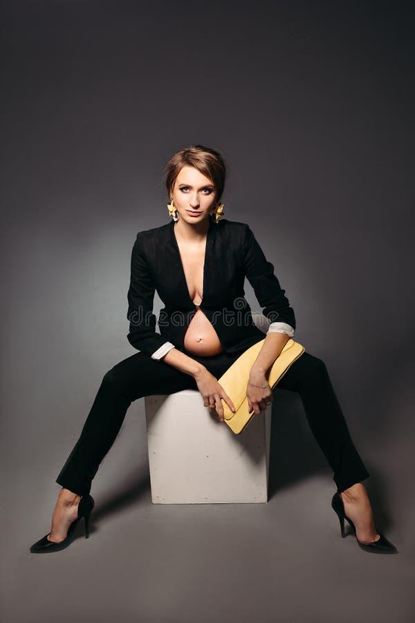 Mulher gravida elegante que veste no terno preto foto de stock royalty free