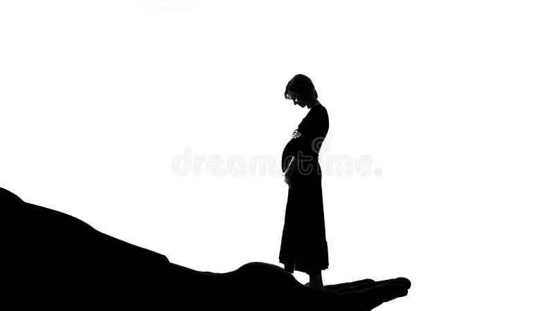 Mulher gravida em sua mão, gratitude da terra arrendada do deus para o cuidado de maternidade, pré-natal fotografia de stock royalty free