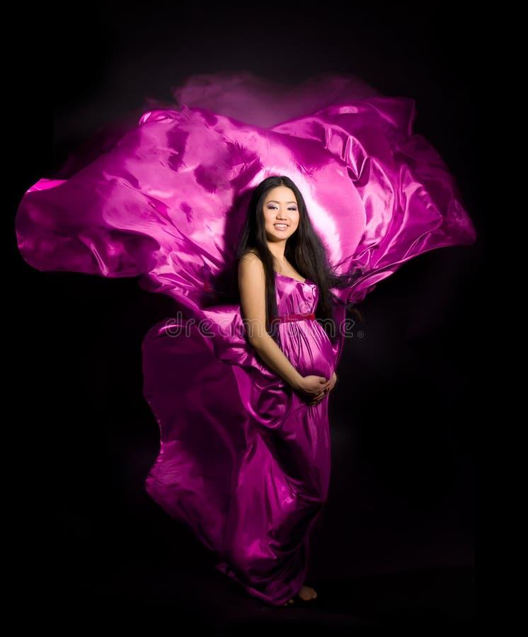 Mulher gravida em um vestido cor-de-rosa