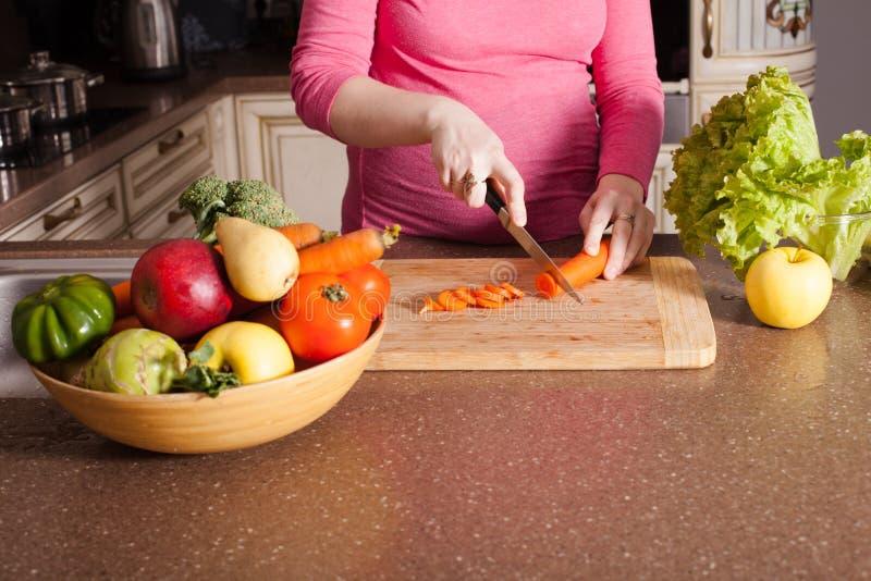 A mulher gravida está cozinhando fotografia de stock royalty free