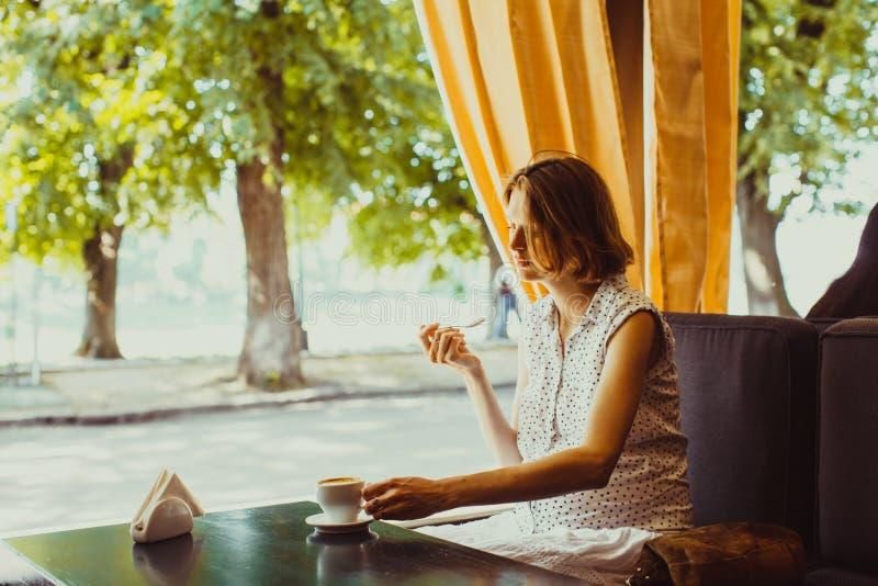A mulher gravida está descansando em um café fotografia de stock