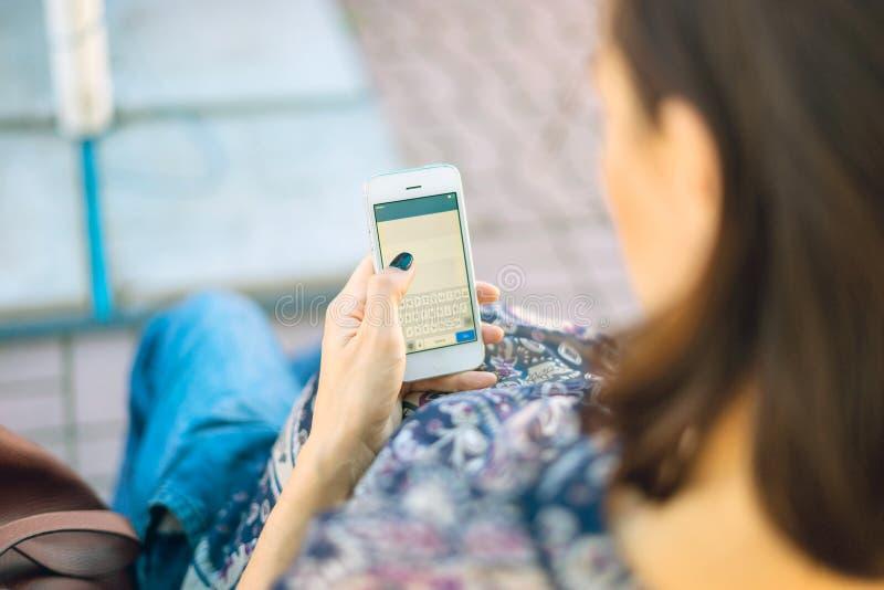 A mulher gravida está guardando um telefone fotos de stock