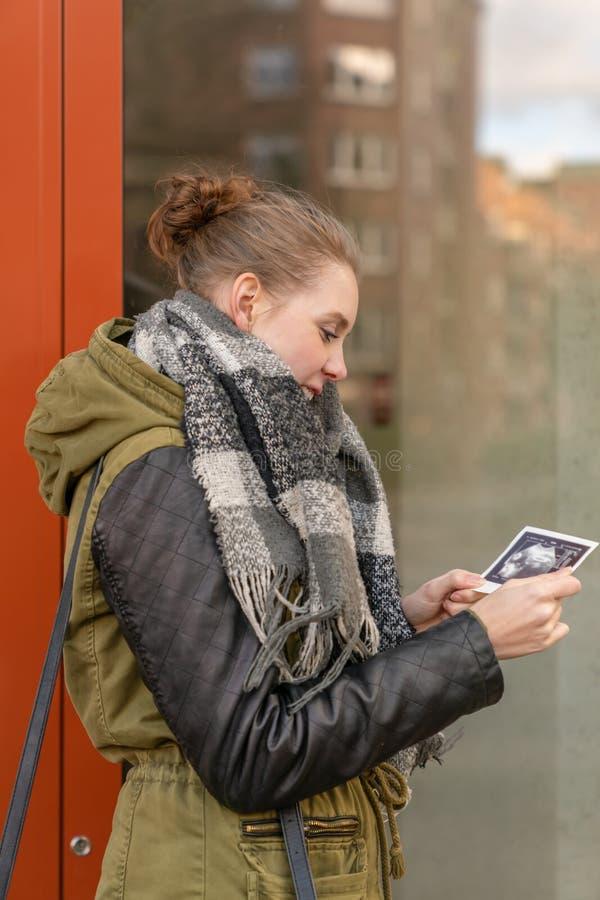 A mulher gravida está guardando um ultrassônico de seu bebê em sua mão fotos de stock