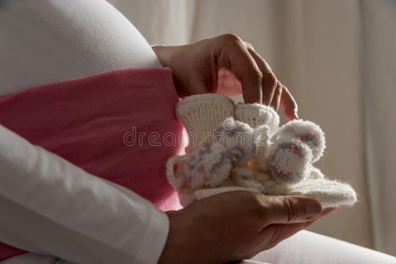 A mulher gravida está guardarando sapatas de bebê imagens de stock royalty free
