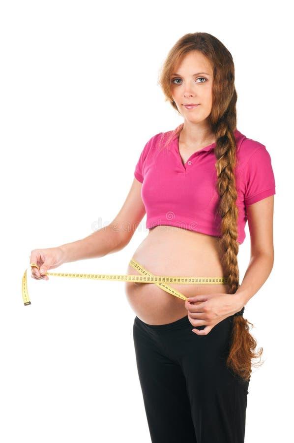 A mulher gravida está medindo seu estômago fotografia de stock royalty free