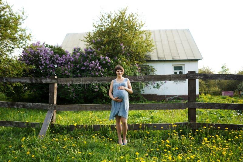 A mulher gravida está relaxando no jardim na casa mulher gravida que guarda suas barriga e flor no jardim foto de stock