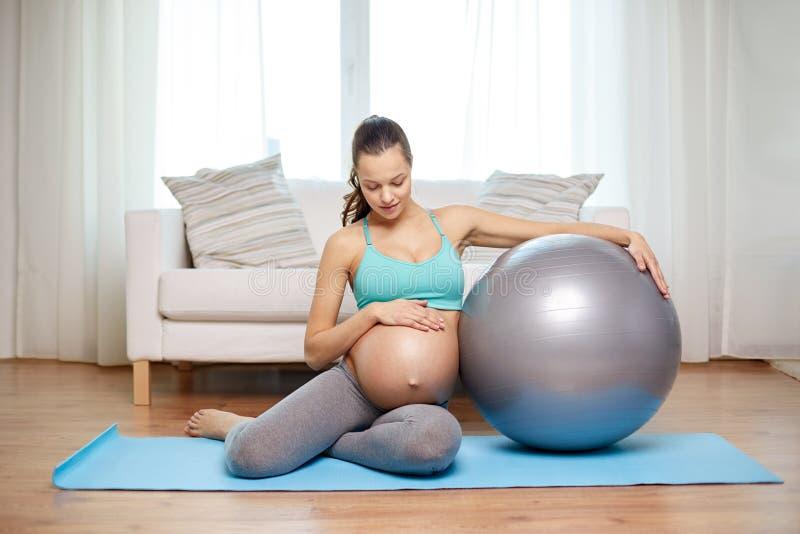 Mulher gravida feliz com fitball em casa imagem de stock