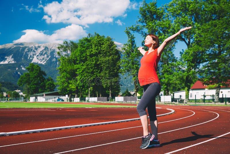 Mulher gravida feliz com mãos levantadas no estádio do esporte fotografia de stock royalty free