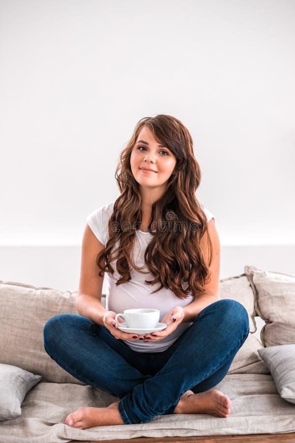 Mulher gravida feliz com o copo do chá fotografia de stock