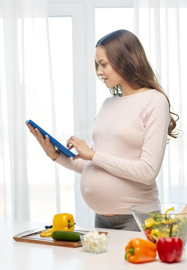 Mulher gravida feliz com PC da tabuleta que cozinha o alimento fotos de stock
