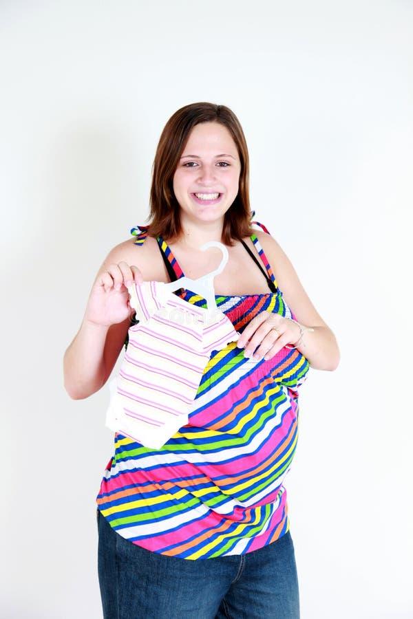 Mulher gravida feliz com roupa do bebê foto de stock