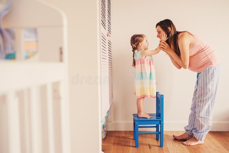 Mulher gravida feliz com sua filha da criança em casa foto de stock royalty free