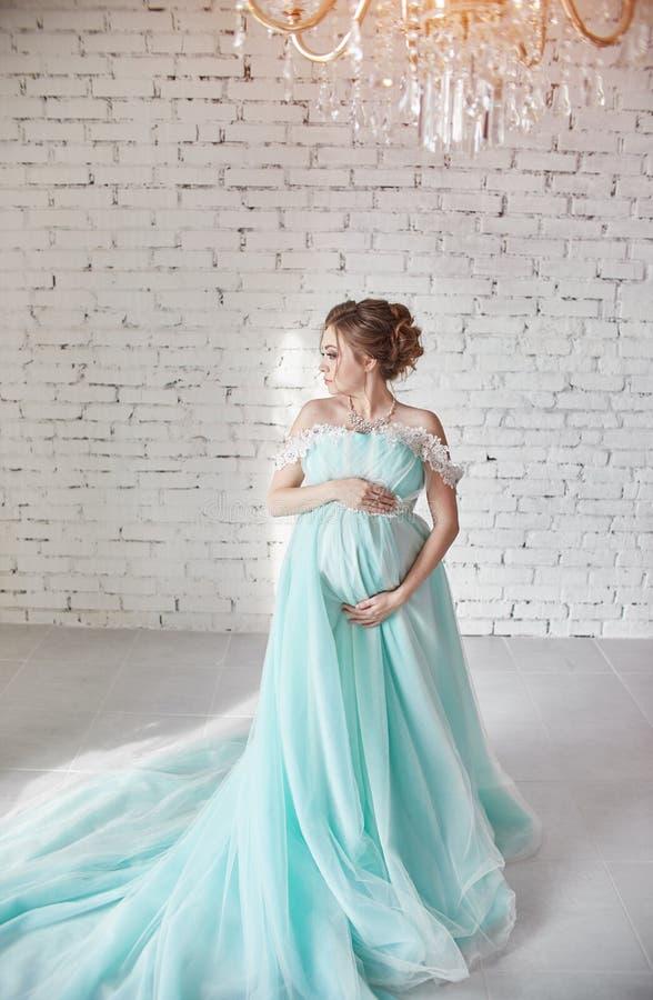 Mulher gravida feliz nas mãos tocantes longas da barriga do vestido de noite Esperando o nascimento de uma criança, uma mulher em fotografia de stock royalty free