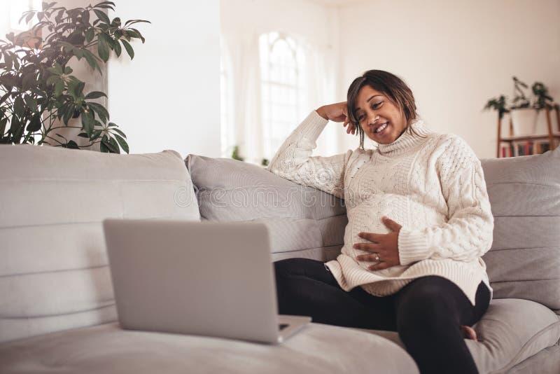 Mulher gravida feliz no sofá usando o portátil foto de stock