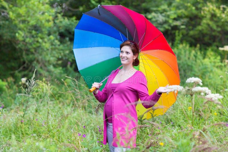 Mulher gravida feliz que anda sob um guarda-chuva colorido fotografia de stock royalty free