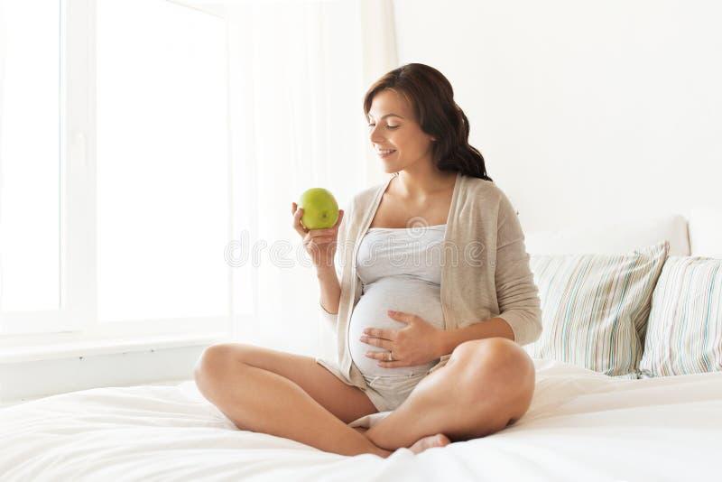 Mulher gravida feliz que come a maçã verde em casa imagens de stock