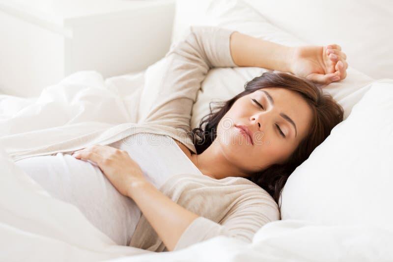 Mulher gravida feliz que dorme na cama em casa fotos de stock