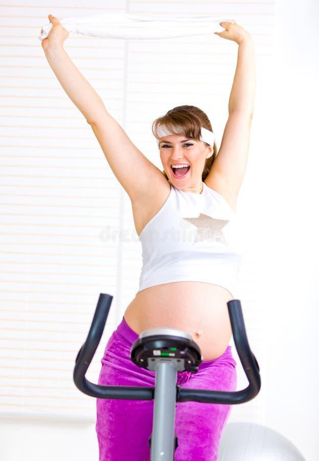 Mulher gravida feliz que elabora na bicicleta foto de stock