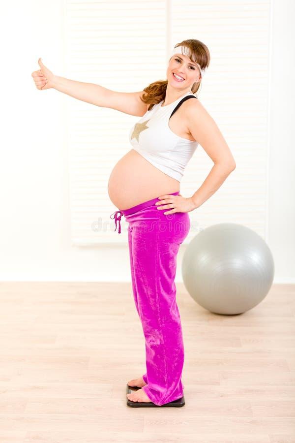Mulher gravida feliz que está na escala do peso foto de stock royalty free