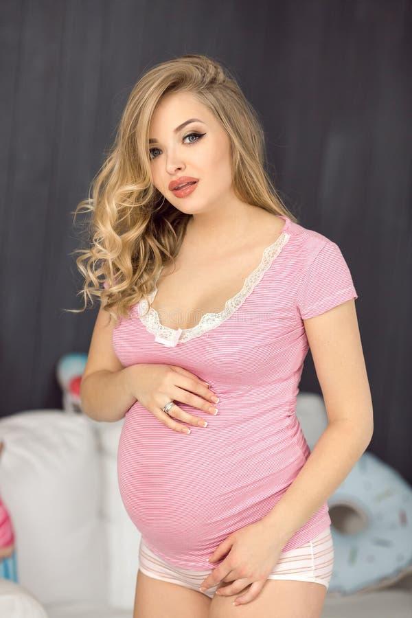 Mulher gravida feliz que levanta na blusa cor-de-rosa Menina 'sexy' do encanto louro novo atrativo em casa fotografia de stock