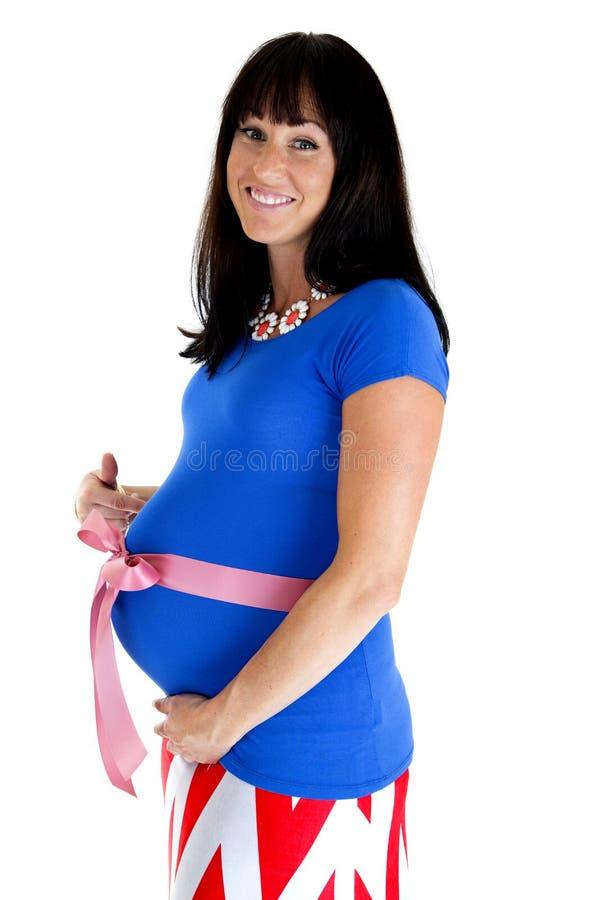 Mulher gravida feliz que mostra fora sua barriga com uma curva cor-de-rosa imagens de stock