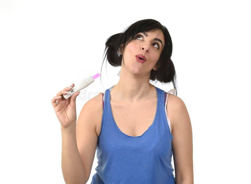 Mulher gravida feliz que mostra o resultado positivo cor-de-rosa no sorriso do teste de gravidez fotografia de stock