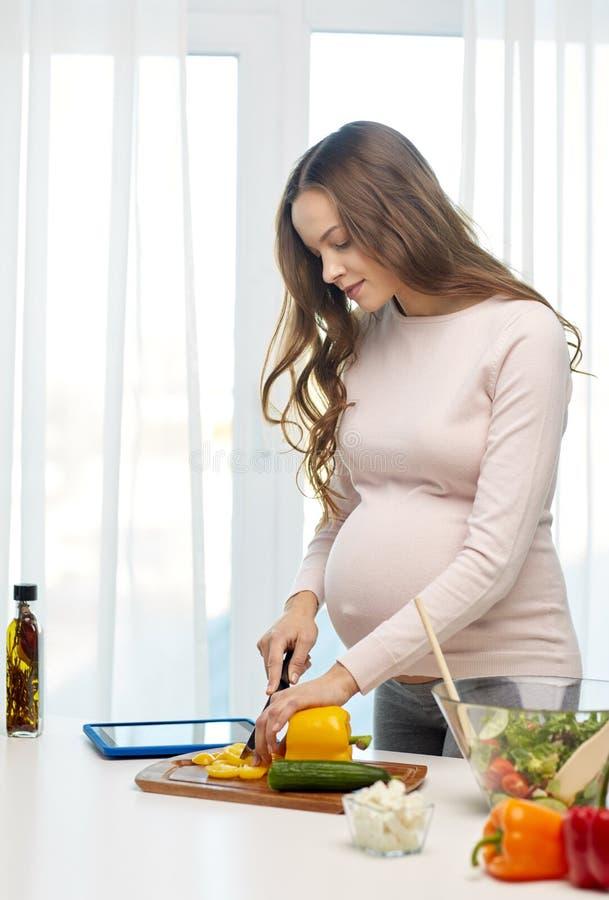 Mulher gravida feliz que prepara o alimento em casa foto de stock