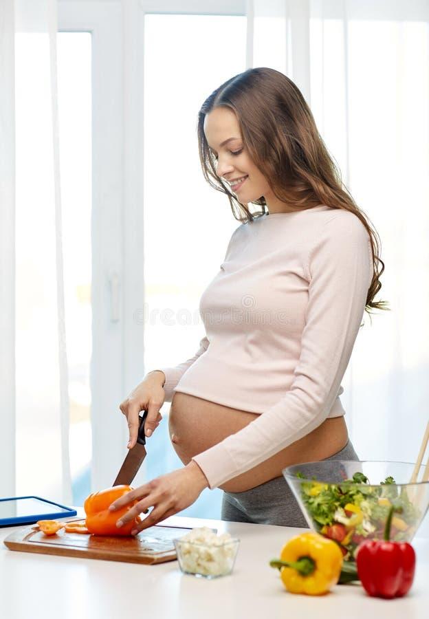 Mulher gravida feliz que prepara o alimento em casa fotografia de stock royalty free