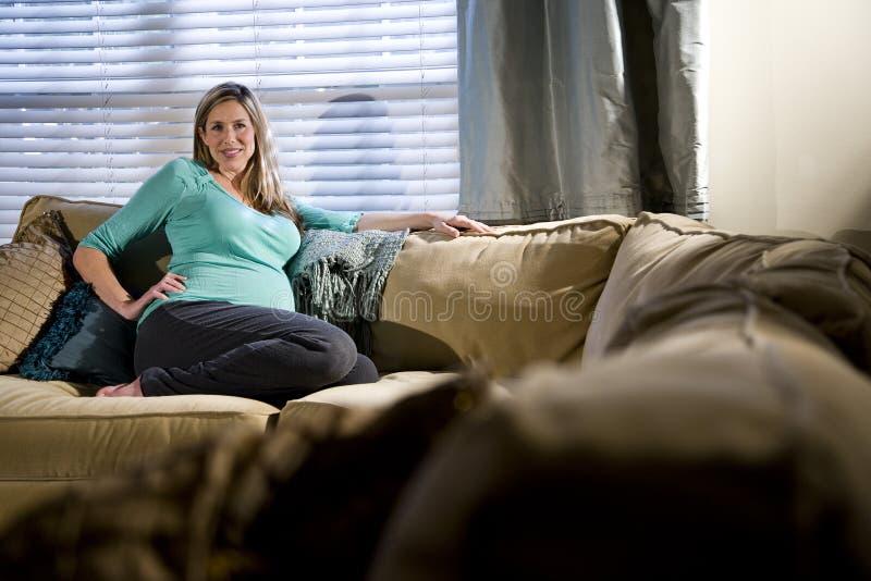 Mulher gravida feliz que relaxa no sofá imagem de stock royalty free