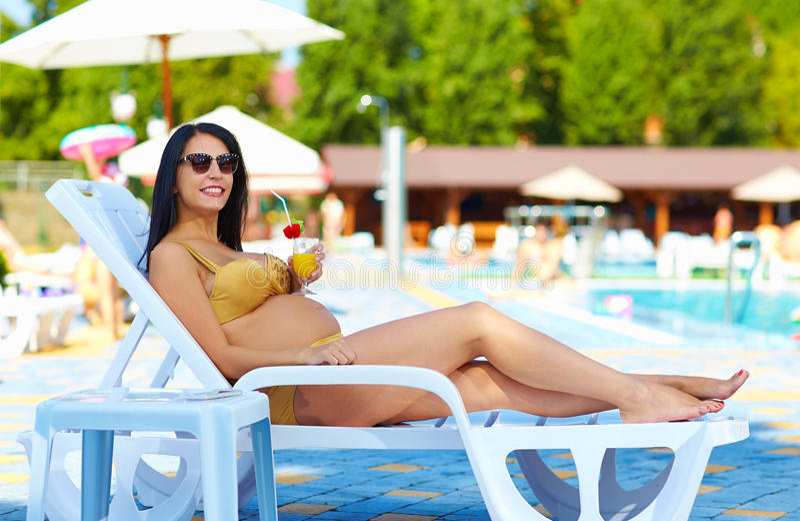 Mulher gravida feliz que relaxa no sunbed fotografia de stock royalty free