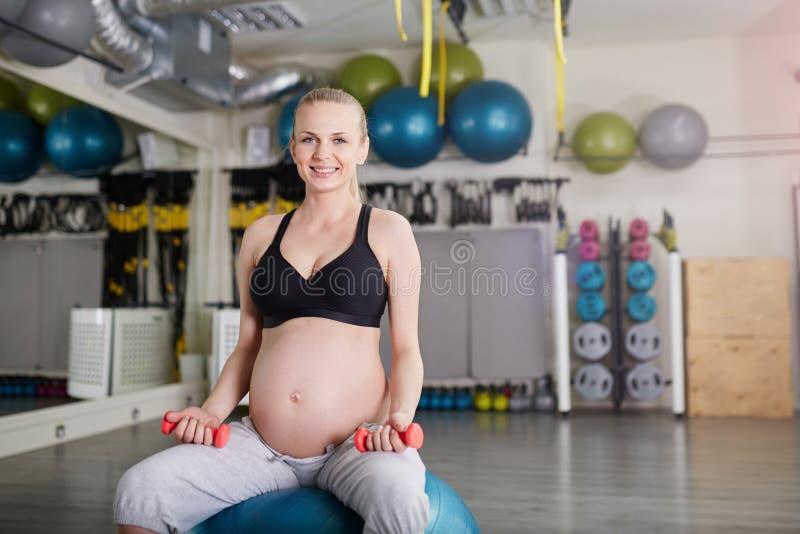 Mulher gravida feliz que senta-se em levantar peso da bola do gym foto de stock royalty free