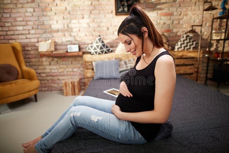 Mulher gravida feliz que senta-se na cama em casa fotografia de stock royalty free