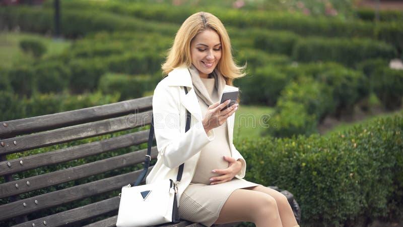 Mulher gravida feliz que senta-se no banco de parque com o smartphone, afagando a barriga imagens de stock