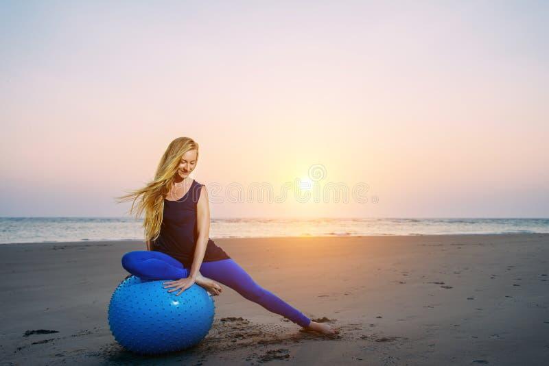 A mulher gravida feliz senta-se na bola do exercício contra o por do sol sobre o mar Gravidez, esporte, aptidão e estilo de vida  imagens de stock royalty free