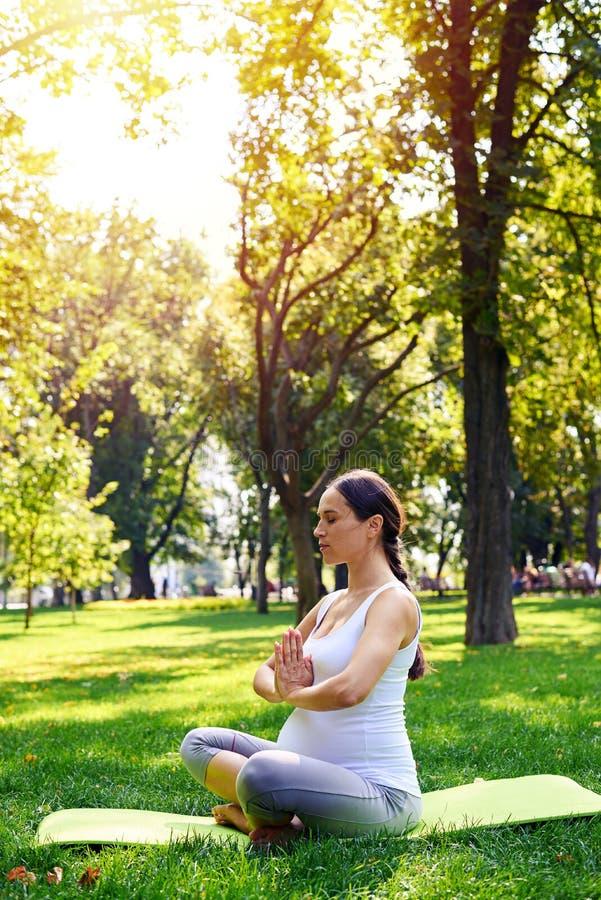 Mulher gravida focalizada que senta-se na pose dos lótus no parque imagens de stock